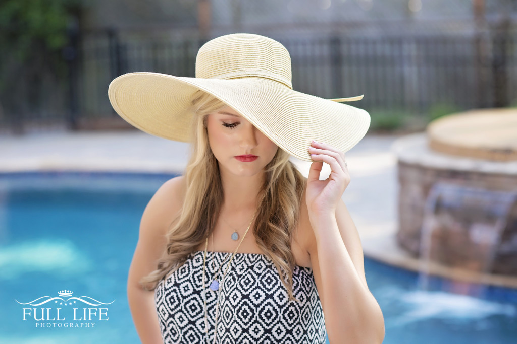 Senior girl by pool with hat